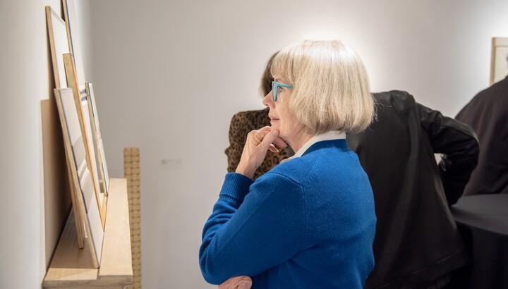 woman examining work of art